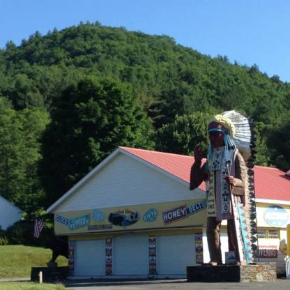 """""""Indian"""" Trading Posts can still be found along MA Rt. 2, otherwise known as The Mohawk Trail--69 miles of """"scenic highway"""" built along former indigenous trade routes that King Philip or Metacom used as he sought the aid of the Mohawk to defeat the English during King Philip's War in the 1670's. The Mohawk Trail, in its tourist heyday, capitalized off highly romanticized lore conflating memories of King Philip's War with Last of the Mohicans motifs and Plains Indian regalia. In the background stands a part of Catamount Hill, possible site of William Apess' birth."""